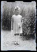girl holding a flower standing in the garden France circa 1930s