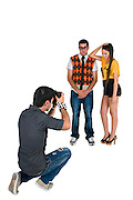 Photographer photographing models on white background