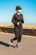 seaside female runner wearing black track suit and white face mask with blue sky on a summers days.