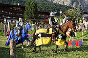 Knights in shining armor ride horses in a medieval festival, in Selva di Val Gardena, Italy. The beautiful ski resort of Selva di Val Gardena (German: Wolkenstein in Gröden; Ladin: Sëlva Gherdëine) makes a great hiking base in the Trentino-Alto Adige/Südtirol (South Tyrol) region of Italy, in the Dolomites, part of the Southern Limestone Alps, Europe. UNESCO honored the Dolomites as a natural World Heritage Site in 2009.