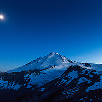 The moon sits above Mt Baker as the last bit of daylight slips away. © John McBrayer