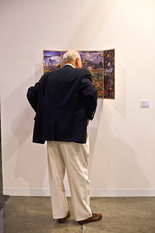 Visitor views triptych at Art Basel Miami Beach 2007