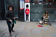 Street scene in Leicester Square of a busker and a Greandier Guard in London, England, United Kingdom. This remains one of Londons tourism hot spots with entertainers and shop and space to hang out.