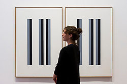 """© Licensed to London News Pictures. 29/10/2020. LONDON, UK.  A staff member poses next to """"Ohne Titel"""", 1977, by Verena Loewensburg. Preview of """"Female Minimal:  Abstraction in the Expanded Field"""", an exhibition of geometric abstract art at Galerie Thaddeus Ropac in Mayfair.  On display are works by 13 female artists from 10 countries many of whom were previously written out of art history due to their gender or politics at the time.  The show suns 29 October to 18 December.  Photo credit: Stephen Chung/LNP"""