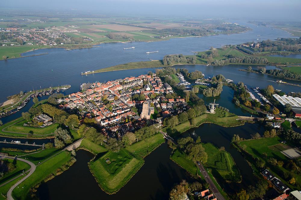 Nederland, Noord-Brabant, Woudrichem, 28-10-2014; vestingstad in Land van Heusden en Altena. Gelegen op de plaats waar de Maas (nu Afgedamde Maas) in de Waal stroomt en verder gaat als Boven-Merwede. In het centrum de Martinuskerk, buiten de stadsmuren molen Nooit Gedagt (korenmolen).<br /> Fortified town in Land of Altena. Located at the place where the Maas (Meuse) flows in the river Waal river, continuing under the name of Boven-Merwede. In the center church of Saint Martin, outside the city walls the mill Never thought fit (flour mill)<br /> luchtfoto (toeslag op standard tarieven); aerial photo (additional fee required); copyright foto/photo Siebe Swart