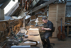 Worker making violin at workshop