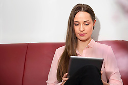 Young woman sitting sofa tablet computer studying