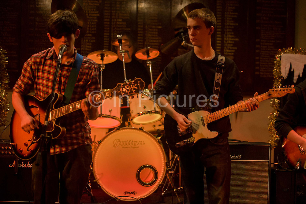 Teenager boys sing and play the guitar during a live gig in south London, UK. The two frontmen play their musical arrangements of a Beatles cover, their lead and rhythm guitars together along with a drummer in the background. The lads are 15 years-old and have  rehearsed this song for weeks beforehand by their guitar teacher and given the opportunity to play in front of a small audience. The boy on the left is the vocalist, a singer taking the lead role in the 4-piece band, while the kid on the right looks across to the singer, checking tempo and when the next chord change occurs.