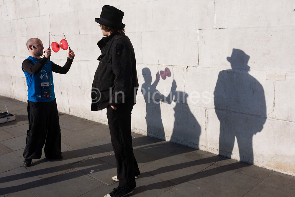 """Two buskers have been questioned by a police officer, their shadows played on a stone wall in Trafalgar Square. As the conversation draws to a close, the juggler of the two buskers begins to throw his red diabolo top into the air and spins it with the help of two sticks. Their respective shadows lend a clue of their numbers, that one extra person (the policeman) is still nearby. The diabolo (commonly misspelled as diablo; formerly also known as """"the devil on two sticks"""") is a juggling prop consisting of a spool which is whirled and tossed on a string tied to two sticks held one in each hand. A huge variety of tricks are possible using the sticks, string, and various body parts."""