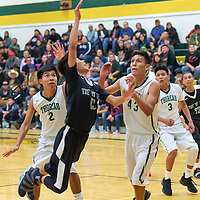 Sheldon Castillo (13) of Tse Yi Gai, drives to the rim with heavy pressure from Dallen Plummer (2) and Donovan Saunders (43) of the Hawks, on Friday night in Thoreau.