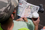 "A labourer reads a copy of Britain's tabloid Sun Newspaper. The worker holds a coffee and wears a working mans' cap with a pencil in his right ear as he sits in sunshine during a lunch break. Page Three (or Page 3) is a tabloid newspaper photograph consisting of a topless female glamour model, usually printed on the paper's third page. Women who model regularly for the feature are known as Page Three girls. ""Page Three"" and ""Page 3"" are registered trademarks of the Sun tabloid, where the feature originated in 1970. In the context of the News International media scandals of 2011, the (daily) Sun is a sister paper to the now defunct (Sunday) News of The World, closed down by proprietor Rupert Murdoch in the light of public outrage over phone hacking."