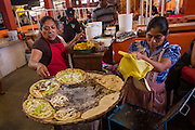 Zapotec women make tacos at the Sunday market in Tlacolula de Matamoros, Mexico. The regional street market draws thousands of sellers and shoppers from throughout the Valles Centrales de Oaxaca.