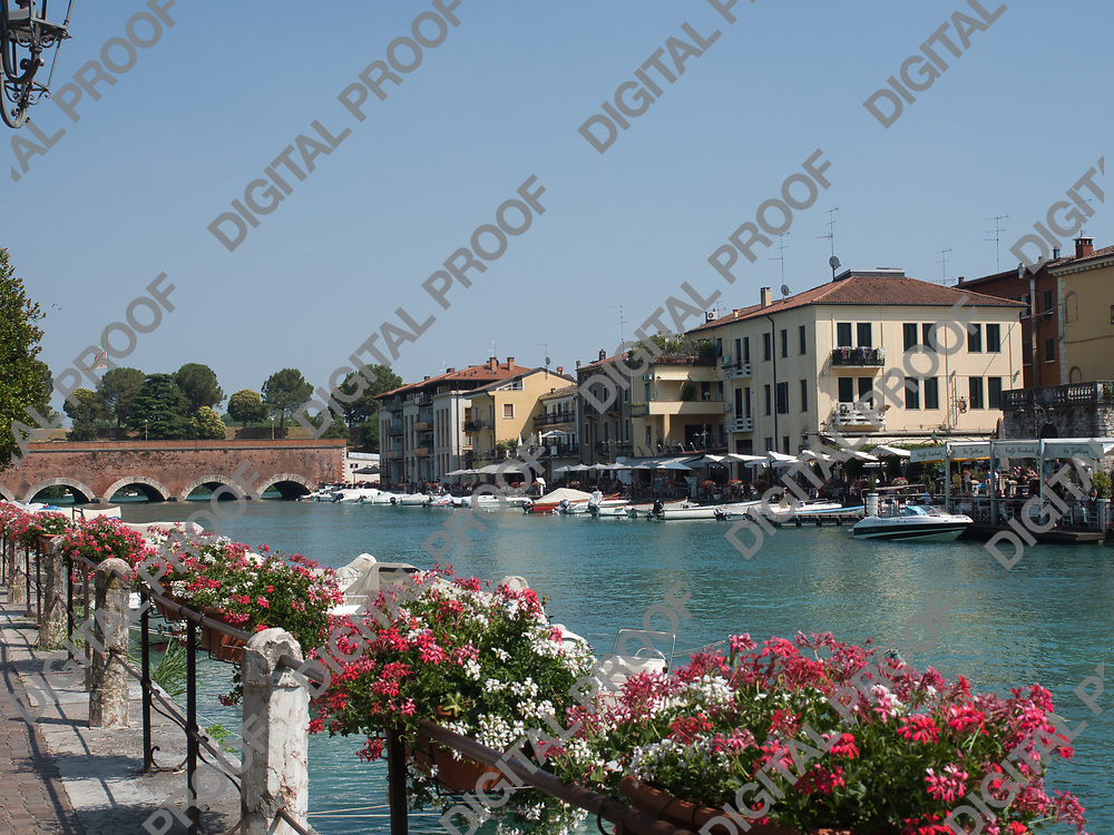Motorboats parked along the peschiera del garda canal in lake garda, italy during a summer afternoon with clear skies with local businesses in the background and flowers at foreground