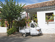 Small three wheeled truck vehicle outside village house Grazalema, Spain