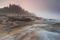 Fog rolls in at sunset along the rocky coastline of Cape Breton island, Nova Scotia, Canada