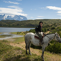 A young gaucho rides his horse in Torres del Paine National Park, Chile.