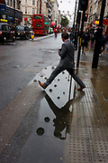 A man steps over a puddle after rainfall in Oxford Street, central London. The day is dark and grey in autumnal weather and it feels like a dystopian landscapoe of dirty pavements (sidewalks) and road surfaces. Reflected in the puddle we see spherical lighting features ready for a forthcoming Christmas, echoed on the raised kerbside buttons that help pedestrians cross safely. We see the person half-way across the width, before landing still dry the other side.