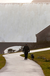 © Licensed to London News Pictures. 16/02/2020.  Rhayader, Powys, Wales, UK. A man walks a dog as torrents of water cascade furiously over the Caban Coch reservoir dam in Elan valley after extremely heavy rainfall in Powys yesterday, last night and today. Photo credit: Graham M. Lawrence/LNP