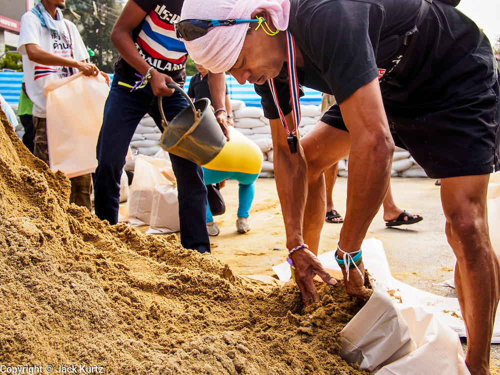 "30 DECEMBER 2013 - BANGKOK, THAILAND: Anti-government protestors fill sandbags to place across Ratchadamnoen Road in Bangkok. Violence around the anti-government protest sites has escalated in recent days and several protestors have been hurt by small explosive devices thrown at their guard posts. As a result, protestors are fortifying their positions with sandbags and bunkers. Suthep Thaugsuban, the leader of the anti-government protests in Bangkok, has called for a new series of massive protests after the 1st of the year and said it the shutdown, or what he described was the seizure of the capital, would be the day when ""People's Revolution"" would ""begin to end and uproot the Thaksin regime.""          PHOTO BY JACK KURTZ"