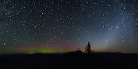 Northern lights dance in the north and the zodiacal light shines in the east. This view was seen from the 6700 foot summit of Cougar Peak in Montana. This sky was untouched by light pollution, allowing the fainter stars and aurora to be visible. This 4 shot panorama covers a large portion of the sky.