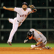 Jun 5, 2013; Houston, TX, USA; Houston Astros second baseman Jose Altuve (27) turns a double play over Baltimore Orioles third baseman Manny Machado (13) during the eighth inning at Minute Maid Park. Mandatory Credit: Thomas Campbell-USA TODAY Sports