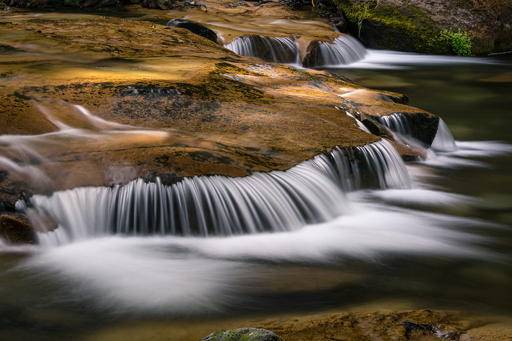 The waters of an unnamed creek flow over granite bedrock in the Cascade Range of Oregon.