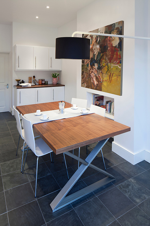 Modern dining table in white dining room with print on wall and overhanging floor lamp