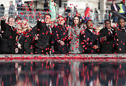 Members of the public throw poppies in the fountain during an event in London's Trafalgar Square to mark Armistice Day.