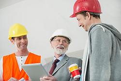 Architect, building owner and construction worker at construction site of new building