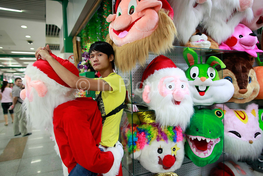 A young man wearing a trick Santa Claus costume wait for customers outside of his stall at the Yiwu International Trade City in Yiwu, Zhejiang Province, China on Sunday, 11 September 2011.   As the trading hub for small and medium manufacturers and exporters in the Yangtze River Delta region, Yiwu faces an uncertain future as export orders decline due to the slow economic recoveries of China's two largest trading partners, Europe and the United States
