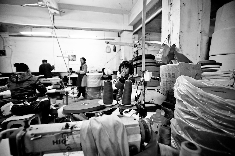 CHONGQING, CHINA - DECEMBER 31, 2010: workers in a textile factory. Often the sons of the workers linger and play around and inside the factories while their parents work