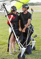 Hang glider pilot Thomas Atkins, right, talks to Emmanuelle Dimarsky before they were towed into the sky by an ultralight aircraft at Randall Airport in Middletown on Friday, Aug. 23, 2013. The hang glider rides are run by Hangar 3.
