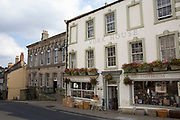 Richmond is a market town and the centre of the district of Richmondshire. Historically in the North Riding of Yorkshire, it is situated on the edge of the Yorkshire Dales National Park. North Yorkshire, England, UK. Local shops in Trinity Church Square.
