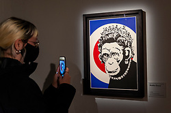 """© Licensed to London News Pictures. 18/05/2021. LONDON, UK. A visitor views """"Monkey Queen"""", 2003, by Banksy. Preview of """"The Art of Banksy"""" at Seven Dials, Covent Garden. Over 100 pieces of Banksy's works are on display from private collections across the globe and it is the first time the world's largest touring exhibition of authentic Banksy Artworks has come to the UK, deferred from 2020 due to the coronavirus pandemic but opening now as lockdown restrictions are eased.  The show runs 20 May to 21 November 2021.  Photo credit: Stephen Chung/LNP"""
