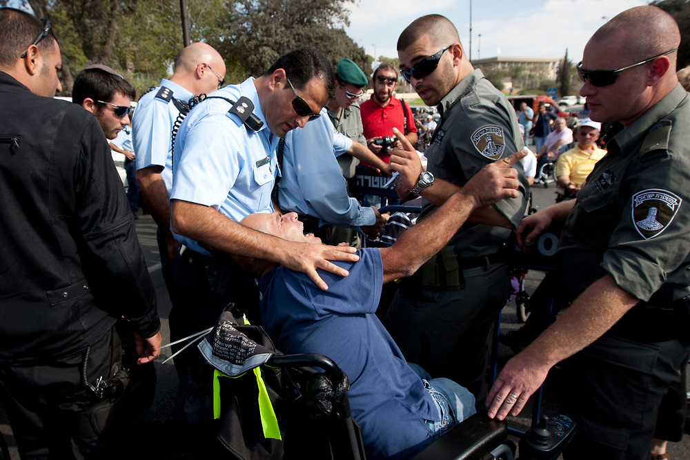Handicapped and disabled people scuffle with Israeli police during a demonstration outside the Finance Ministry and Social Affairs Ministry offices in Jerusalem, on October 25, 2010. The protesters demanded that their disability benefits be increased to the level of the minimum wage.