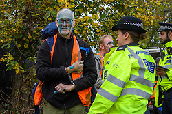 """© Licensed to London News Pictures. 27/10/2021. London, UK. A police officer stands with a detained person as protesters from climate campaign 'Insulate Britain', an offshoot of Extinction Rebellion (XR), block traffic on the A40 Western Avenue in Acton. Following a national injunction covering England's highways, Insulate Britain declared the M25 """"a site of nonviolent civil resistance"""" vowing to return to the motorway network to continue their protest action. Photo credit: Peter Manning/LNP"""