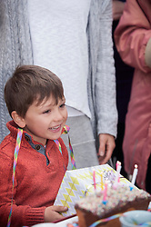 Little boy holding gift at his birthday party and smiling, Bavaria, Germany