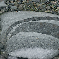 New snow  coats a granite boulder on Booth  Island, Antarctica. The slices are probably from freezing and thawing.