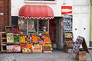 A grocery shop with fruits and vegetables on display on the pavement oranges, apples, bell peppers, chalk boards advertising the products. Montevideo, Uruguay, South America