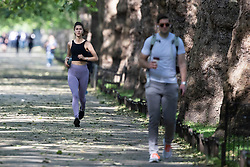 © Licensed to London News Pictures. 08/06/2021. London, UK. A woman jogs during sunny weather in St James's Park in Central London. Temperatures are expected to rise with highs of 23 degrees forecasted for parts of London and South East England today . Photo credit: George Cracknell Wright/LNP