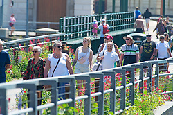 © Licensed to London News Pictures 14/06/2021. Folkestone, UK. People heading to the beach. The hot heatwave weather continues today in Kent as people enjoy the sun in Folkestone Harbour. Photo credit:Grant Falvey/LNP
