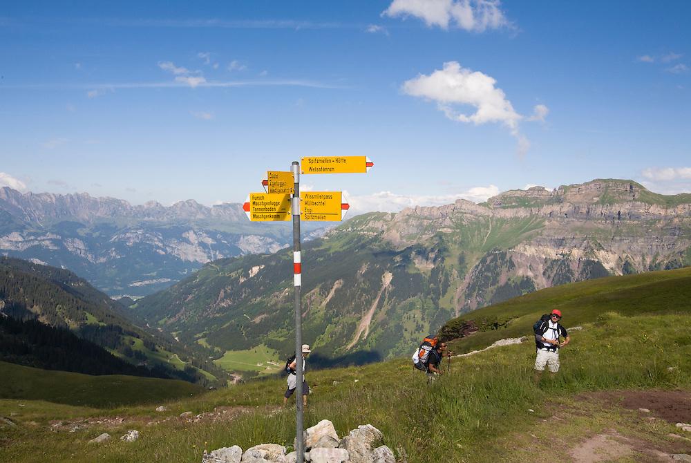 Hikers approaching a crossroads in the Swiss Alps, Flumserberg, Sarganserland, Switzerland