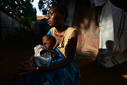 July 6, 2017 - Wau, Wau, South Sudan - JUSTINA MARCO, 27, holds her son EDMOND, 1, who is severely malnourished, as she talks about the life they are facing as displaced people living in a camp in Wau, South Sudan, where nearly 2 million people are displaced and near starvation, according to U.N. figures. Justina said her husband abandoned the family during the clashes, and that she now veers between asking God for help and blaming God for their situation. Her son is very fragile, and she has tried get a priest to Baptize him, only the authorities keep asking where is his father. People in the camp whisper about her. (Credit Image: © Miguel Juarez Lugo/zReportage.com via ZUMA Wire)