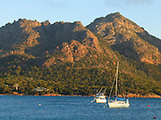Boats anchor in Coles Bay beneath peaks of the Hazards in Freycinet National Park, Tasmania, Australia. Devonian Granite is the dominant rock type at Freycinet. Orthoclase, a pink feldspar gives the mountains and coastline their characteristic pink tint. Black micas and white quartz are also found. The Tasman Sea is part of the South Pacific Ocean.