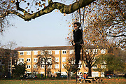 A man exercises on rings suspended from a tree in London Fields during the second coronavirus national lockdownon on 7th of November 2020, Hackney, East London, United Kingdom. London Fields is used by many for exercise and socializing, especially in the time of lockdown. The UK Government introduced a 4 week lockdown from November 5th - December 2nd to combat the coronavirus outbreak. It is the third day of the national lockdown restrictions mean that people are only allowed to meet outside, in pairs and only if keeping social distance. Only if they already live together or have formed a social bubble can they interact freely.
