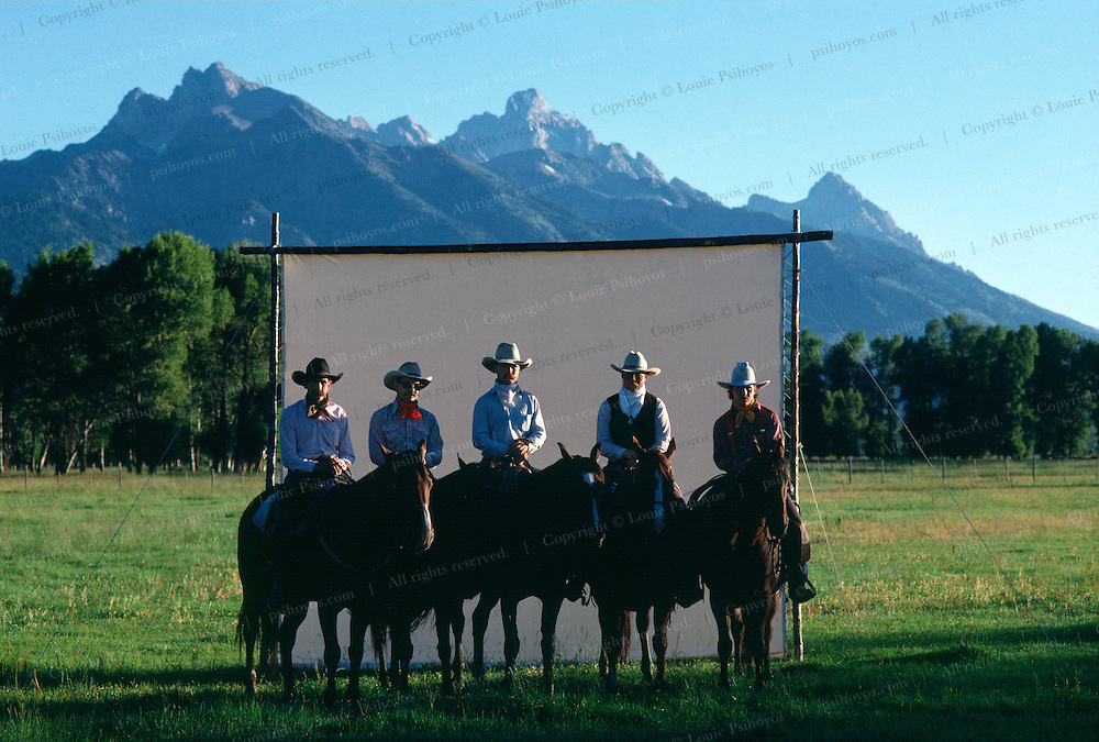 Cowboys of the Snake River Ranch, Wyoming with Tetons in the background.