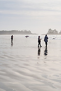 Surfers and tourists enjoy the late afternoon light at low tide on Chesterman Beach in Tofino, British Columbia