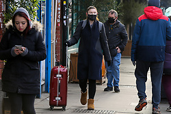 "© Licensed to London News Pictures. 09/01/2021. London, UK. A woman wearing a protective face covering is seen with a travel suitcase in north London as Covid-19 lockdown continues. Prime Minister Boris Johnson has said that the public should ""stay at home"". Photo credit: Dinendra Haria/LNP"