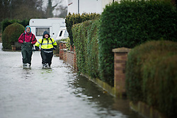© London News Pictures. 12/02/2014. Egham, UK.  Residents of Egham in Surrey walk through flood water. Torrential rain in the area is due to raise water levels increasing the risk of further flooding. Photo credit : Ben Cawthra/LNP