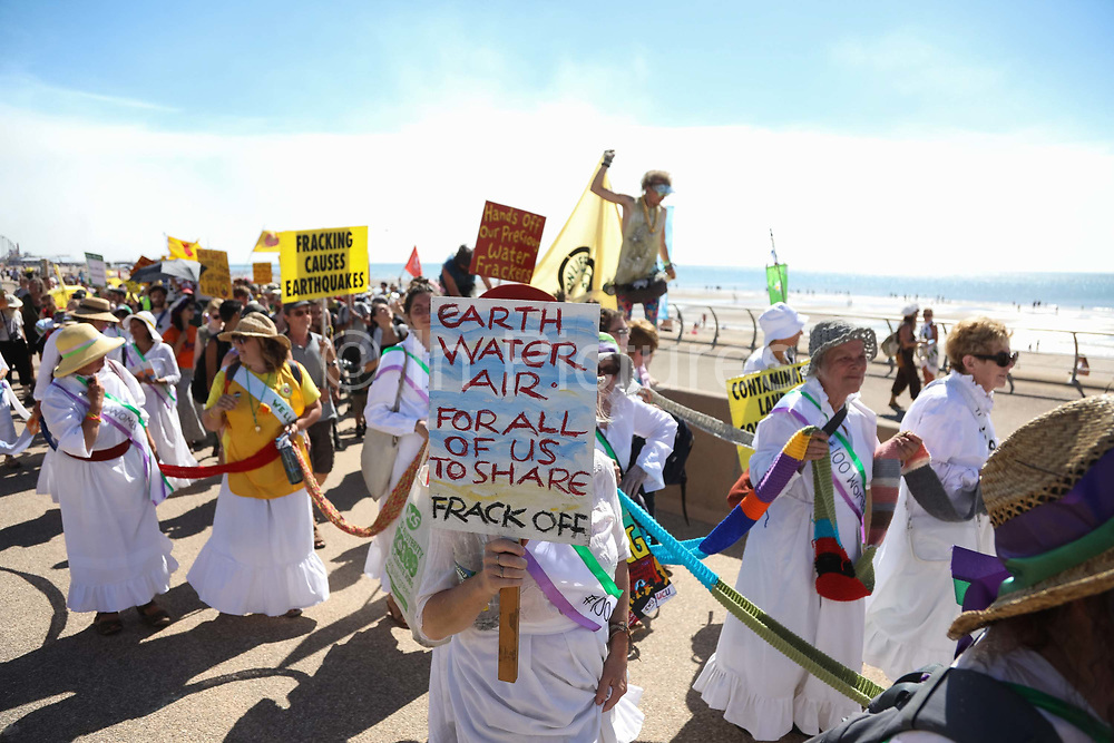 Anti-fracking campaigners march along Blackpool sea front as part of the Block Around the Clock event in Lancashire, United Kingdom, June 29th 2018.  Block Around the Clock - a fourty eight hours of event with work shops, yoga, sleeping and anti-fracking campaigning in front of the gates to Cuadrillas fracking site in Lancashire. The event was organised by anti-fracking campaigners in spite of an injunction granted to Cuadrilla to prevent protest against the impending shale gas exploitation. The Cuadrilla site in Lancashire in a highly contested site, almost ready to drill for gas.